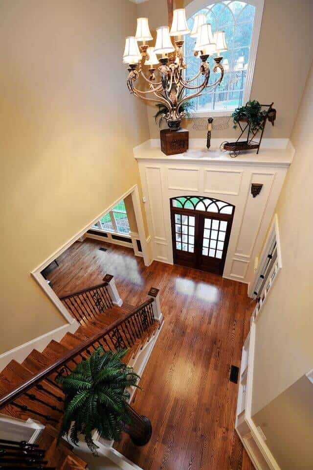 A top view look at this foyer boasting high ceiling with a hanging fancy chandelier. It has a wooden staircase that complements with the hardwood flooring.