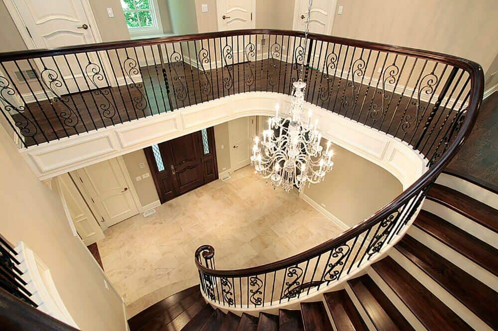 This beige foyer with marble flooring is illuminated by a gorgeous crystal chandelier that's surrounded with a dark wood curved staircase.