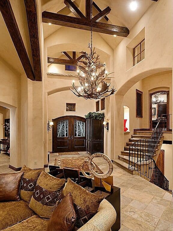 Cozy foyer with limestone flooring topped with vintage rugs and cathedral ceiling with exposed wood beams and a hanging antler chandelier.
