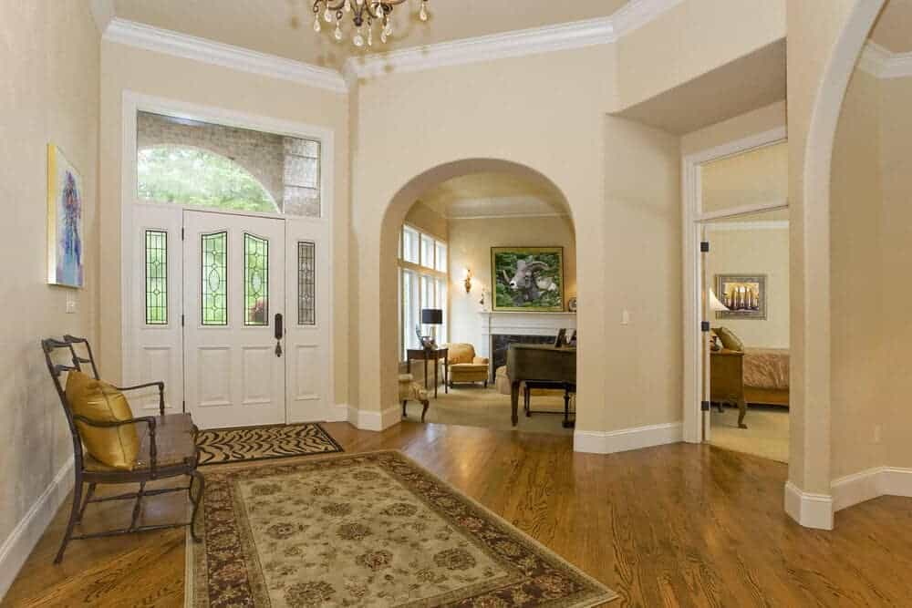 Well lit foyer with beige walls mounted with a wall art canvas and lined with base and crown moldings. It includes a white entry door and wooden chair accented with a gold pillow.
