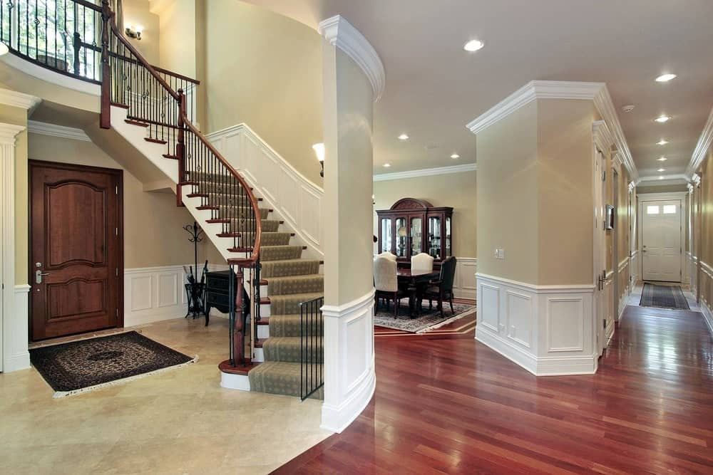 This foyer features a wooden front door along with dark wood console table and umbrella rack situated underneath the curved staircase that's topped with a patterned stair runner.