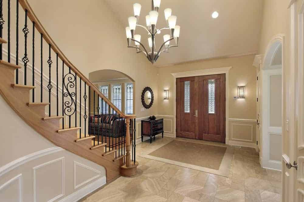 Beige foyer with a wooden console table and round mirror illuminated by wall sconces and chandelier that hung across the wooden staircase.