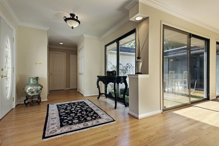 Spacious foyer with glass paneled windows and hardwood flooring topped with a classy floral rug. It includes a dark wood console table and emerald vase by the white front door.
