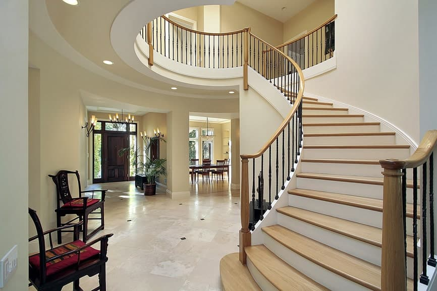 Classic foyer boasts a winding staircase accompanied by a pair of wooden chairs that are topped with red cushions.