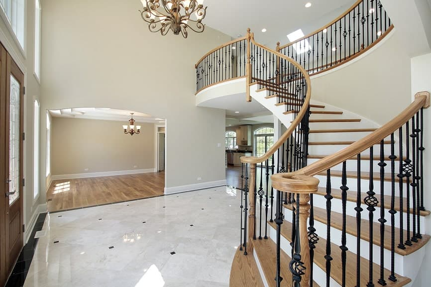 Expansive foyer with elegant marble flooring and a curved staircase framed with wrought iron railings and illuminated by a vintage chandelier.