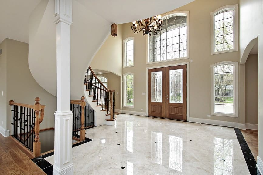 Spacious foyer features an elegant marble flooring and a wooden entry double door surrounded with white framed glass windows.