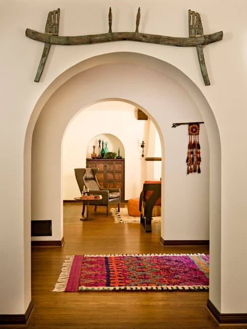 Mediterranean foyer filled with open archways mounted with interesting wall arts along with a lovely tassel rug that lays on hardwood flooring.
