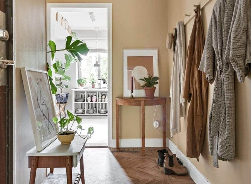 Small foyer filled with wooden console tables topped with framed wall arts and plants along with a coat hook rack mounted on the beige wall.