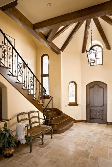 Beige foyer features a wooden seating that complements with staircase framed with ornate balustrade. It has limestone flooring and vaulted ceiling with exposed wood beams.