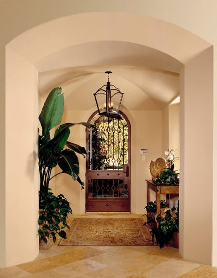Spanish foyer with an arched entry door and wooden console table along with indoor plants that refresh the area.