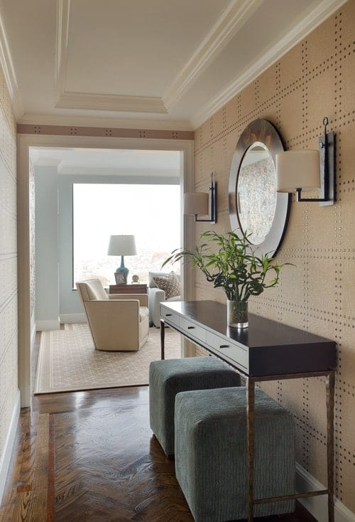 A pair of gray velvet stools sit at a wooden console table in this foyer with a round mirror illuminated by wall sconces.