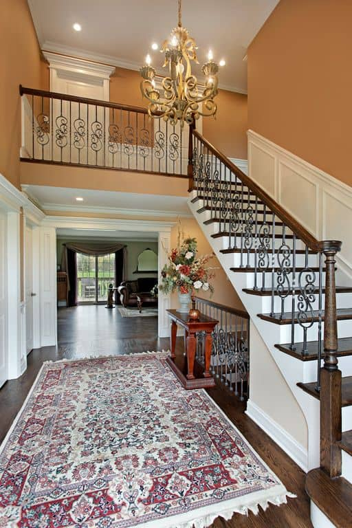 Traditional foyer with an ornate staircase illuminated by a stylish chandelier that hung over redwood console table over the vintage rug.
