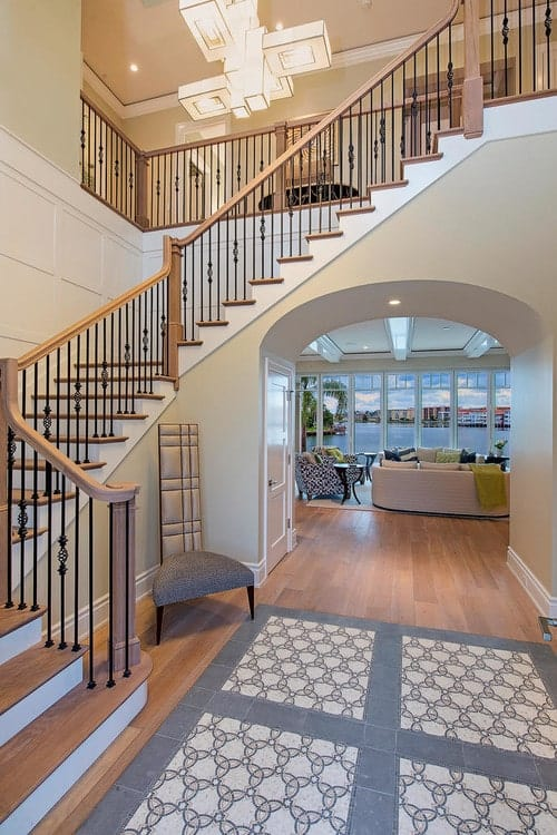 Transitional foyer features a gray high back chair that sits next to the wooden staircase illuminated by a modern chandelier. There's an open archway underneath the stairs that leads to the living room.