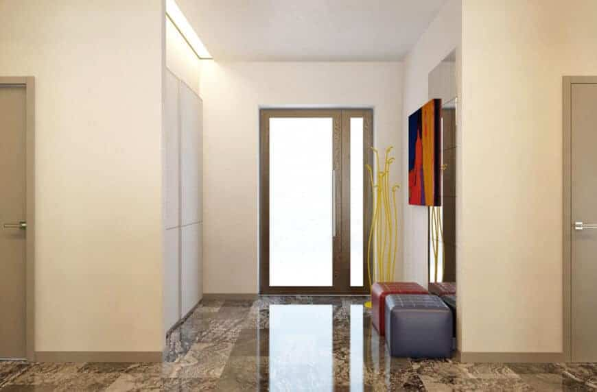 Modern foyer features a colorful wall art that's mounted on the mirror and above red and blue stools over marble flooring.