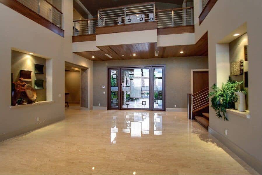 An expansive foyer showcasing inset walls filled with various decors and plants. It has a glass entry door and glossy marble flooring that adds sophistication in the area.
