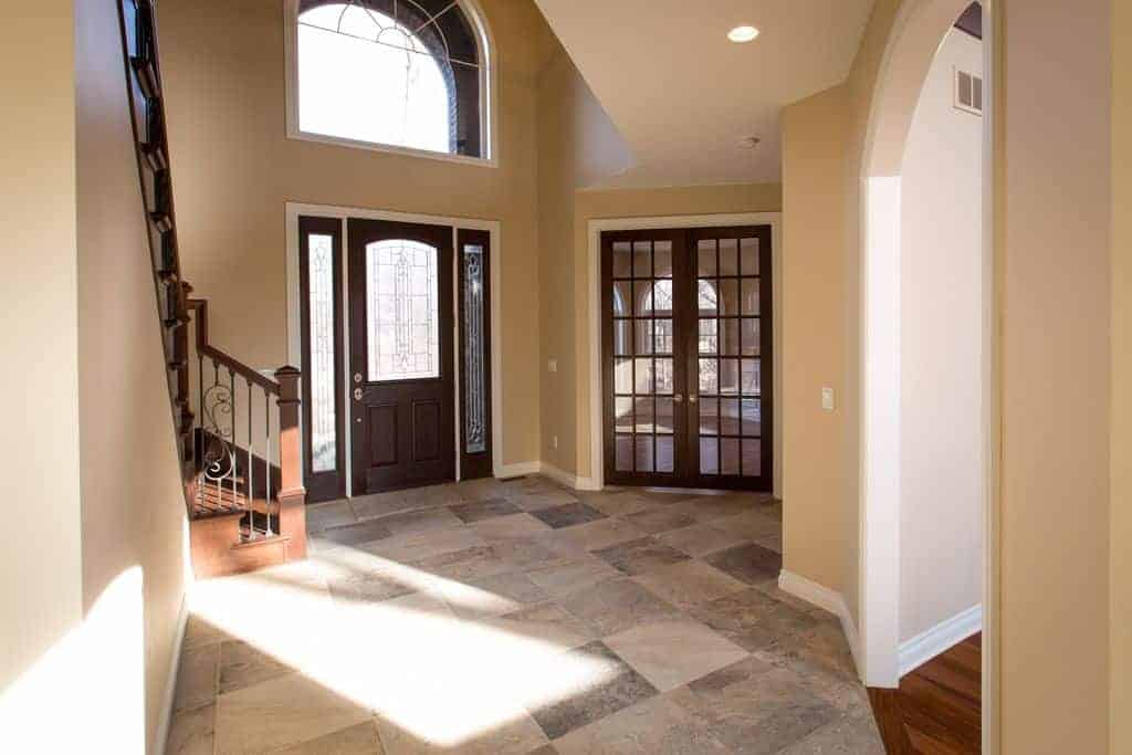 Beige foyer with tiled flooring and wooden staircase along with a french door and dark wood front door fitted with glass panels.