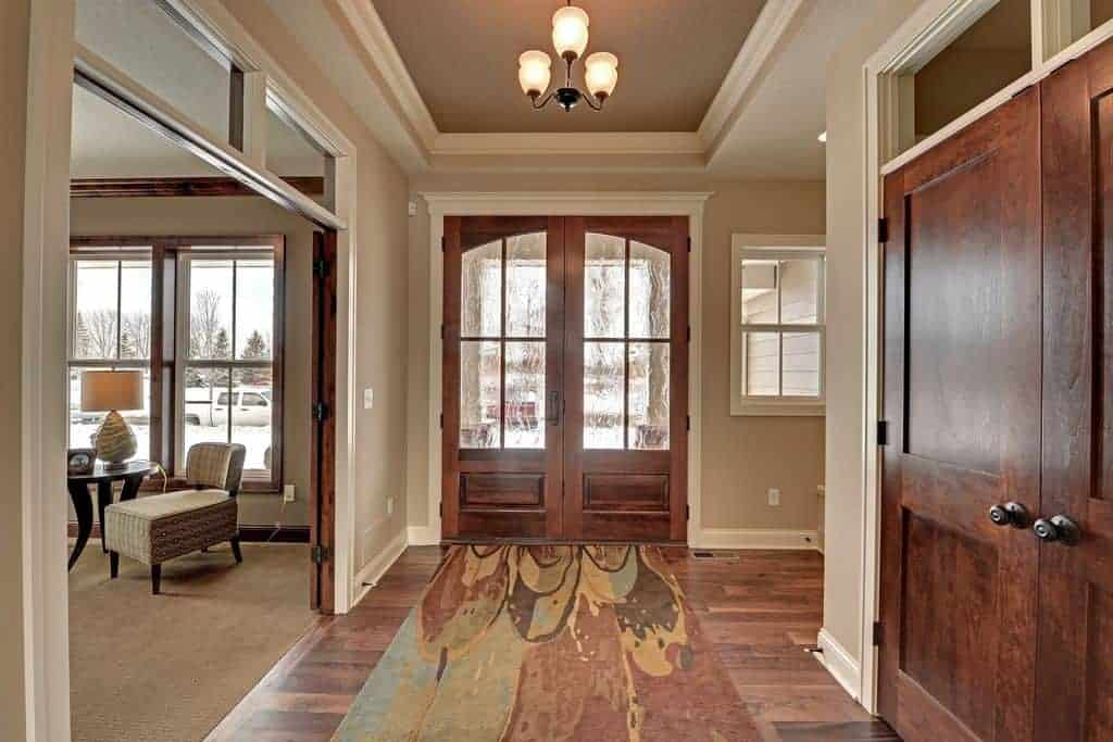 This foyer features a stylish rug leading to the home's living space. The foyer also has hardwood floors and beige walls.