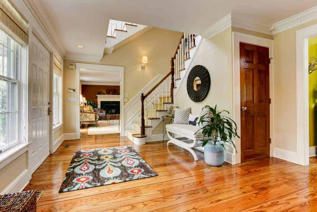 Large foyer boasting hardwood flooring topped by a nice rug. The beige walls are lighted by a wall sconce.