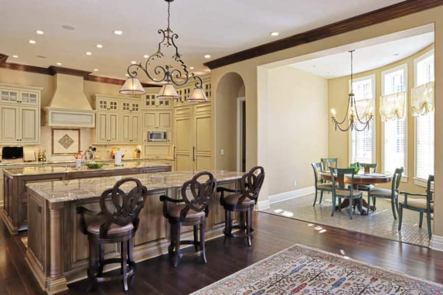 A dine-in kitchen featuring a center island, a breakfast bar island and a dining nook on the side.