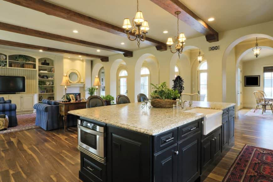 Spacious kitchen featuring a large center island with a marble countertop lighted by small chandeliers hanging from the ceiling with exposed beams.