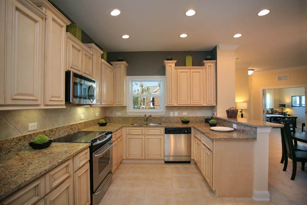 This kitchen features beige cabinetry and kitchen counters along with granite countertops.