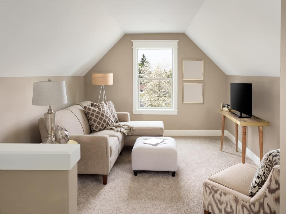 A simplistic and small living space featuring carpet flooring and grayish beige walls. The room also offers an L-shape sofa and a widescreen TV.
