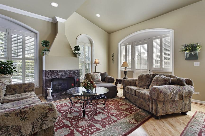 This formal living room boasts elegant seats and classy area rugs covering the hardwood flooring. The room also offers a fireplace.