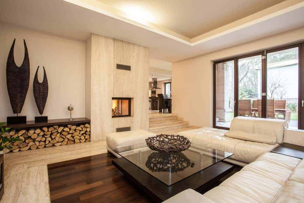 A modish living room featuring stylish flooring and a nice white sofa set with a glass top center table along with a fireplace.