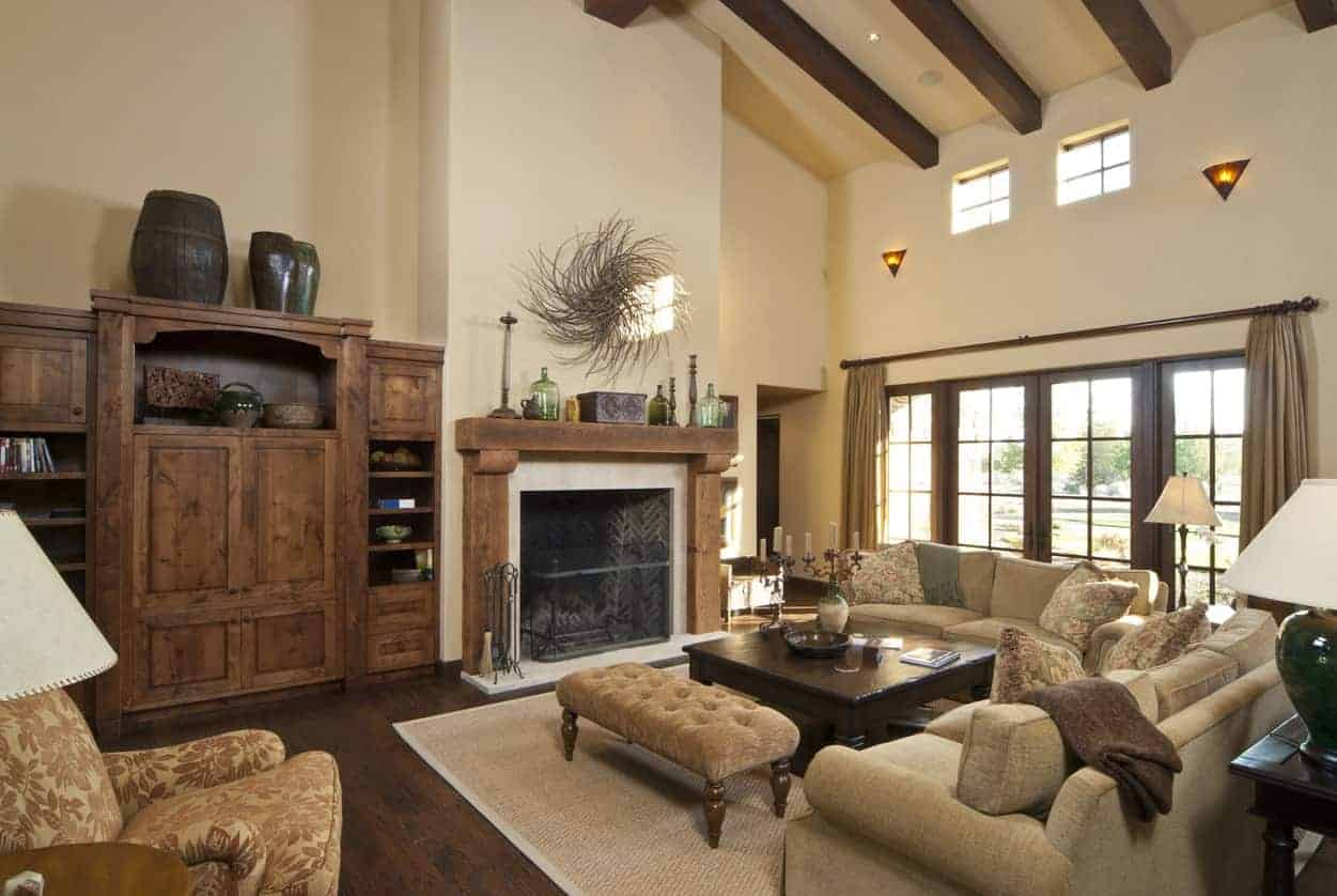 This living room offers a fireplace and rustic cabinetry and shelving on the side. The room has a tall ceiling with exposed beams.
