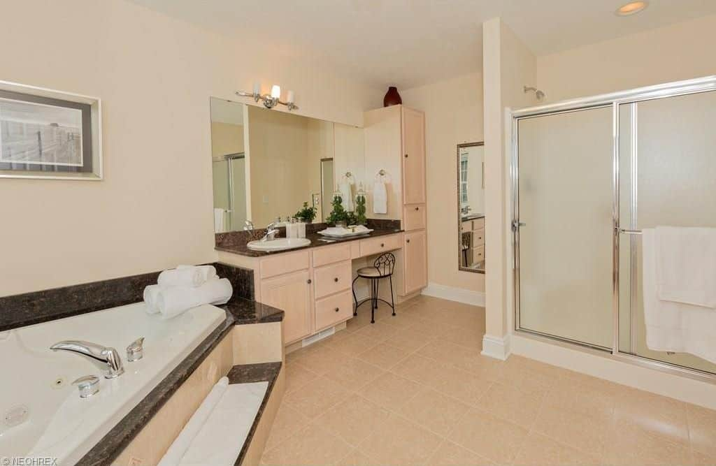 This master bathroom offers a stylish drop-in tub, a powder area and a sink along with a walk-in shower room.