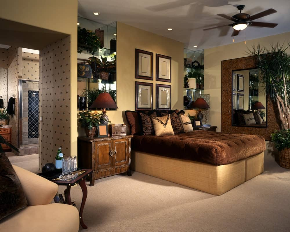 This master bedroom offers a comfy bed along with its own bathroom. The room boasts beige walls and carpet flooring.