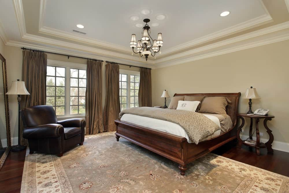 A master bedroom with a large area rug covering the hardwood flooring. The room has beige walls and a tray ceiling lighted by a modish chandelier.