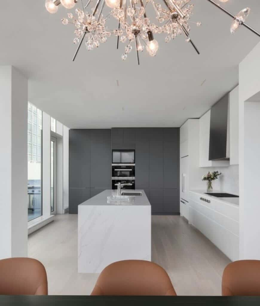 Sleek kitchen boasts white marble breakfast island that sits across the gray storage cabinets fitted with black appliances inset.
