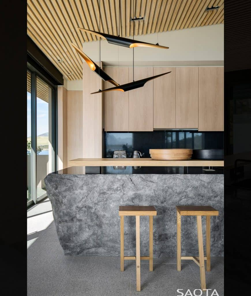 Gorgeous kitchen illuminated by unique and stylish black pendants that hung over a boulder island bar accompanied by wooden stools and cabinetry.