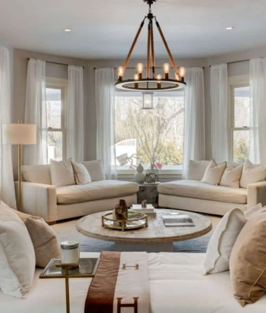 Airy living room showcases a rustic coffee table surrounded with white chaise lounges and illuminated by a round chandelier along with natural light from the glass windows covered with sheer curtains.