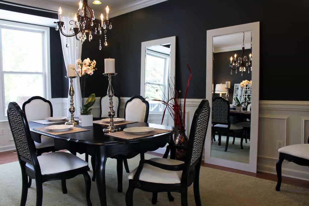 Dining room featuring black and white walls, along with a black dining table and chairs set with a shade of white, set on a large area rug and is lighted by a gorgeous chandelier.