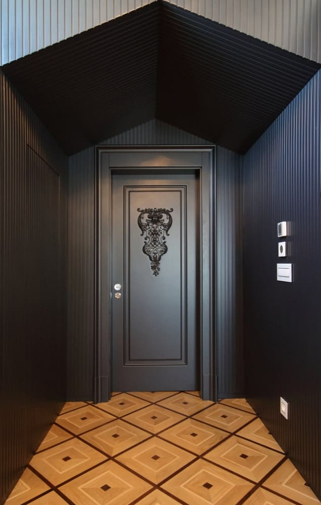 This is a simple black foyer with smooth black walls entending to a low cathedral ceiling. The elegant black wooden door has an intricate wooden art on its face that stands out against the uniformity of the black elements and the patterns of the beige flooring.