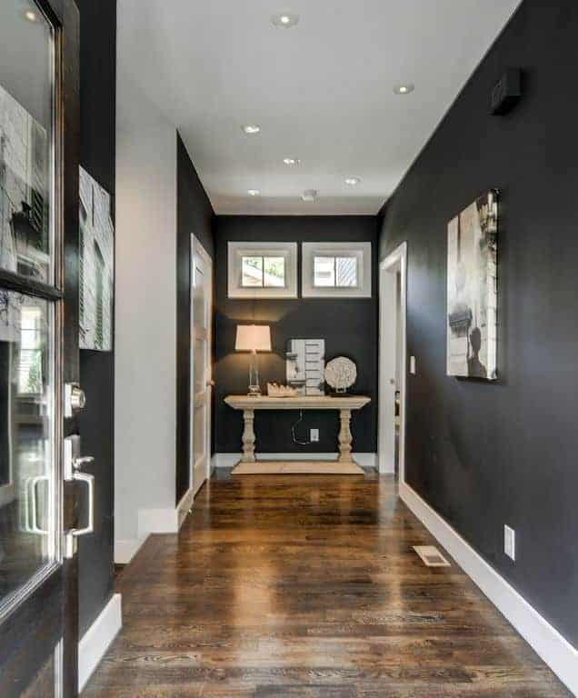 This elegant foyer has black walls that are complemented by dark wood flooring and contrasted by white wooden moldings that line the floor and walls. The dark-walled end of the hallway is adorned with a white marble console table with a table lamp and artworks on it.