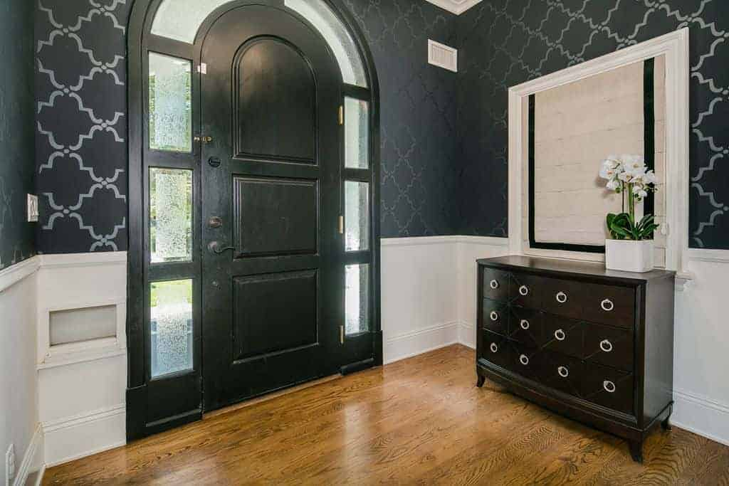 The black wooden door of this simple foyer has an arched top. The sidelights of this main door follow the lay of the arched door with glass panels framed with dark wood. The door matches the patterns of the dark wallpaper and the console table on one side that has built-in apothecary drawers.