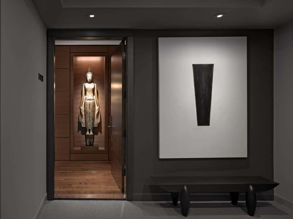This dark walled foyer is adorned with a modern low bench painted as black as the walls. This is topped with a wall-mounted minimalist white artwork illuminated by the pin lights of the black tray ceiling. There is a dramatic Buddhist statuette on the next room that adds flair to this foyer.