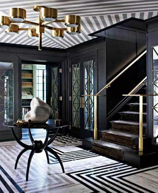 The patterned dark and white marble flooring of this elegant foyer is topped with a modern round black table in the middle. It has a decorative rock on top of it that contrasts the steampunk brass chandelier hanging from the gray-striped ceiling that complements the black walls.