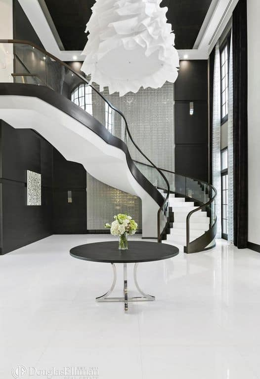 This is a grand foyer that has a delicate balance between black and white elements. The white flooring is topped with a round wooden black table. There is a peculiar white funnel lighting hanging from the black ceiling that is surrounded by white beams. The spiral staircase also follows this aesthetic.