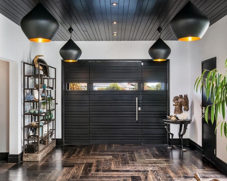 Spacious foyer with a black door and ceiling lighted by four stylish black pendant lights.