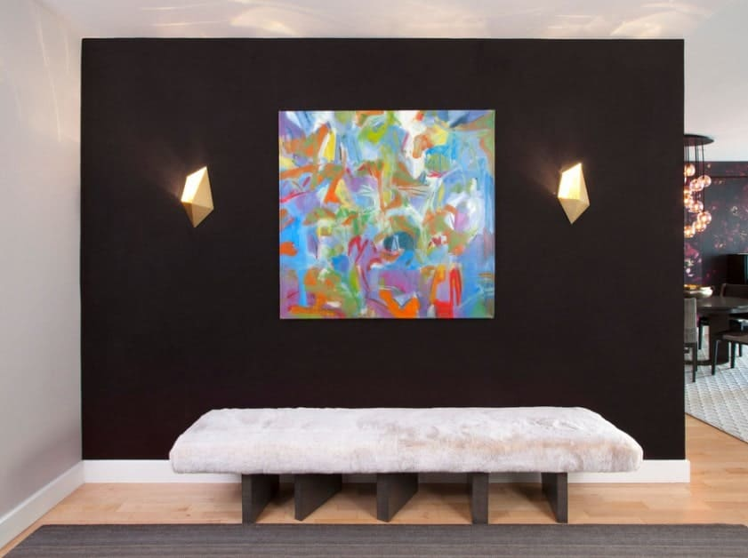 A foyer featuring a nice bench seating along with a black wall on its back with an artistic colorful wall decor lighted by stylish wall sconces.