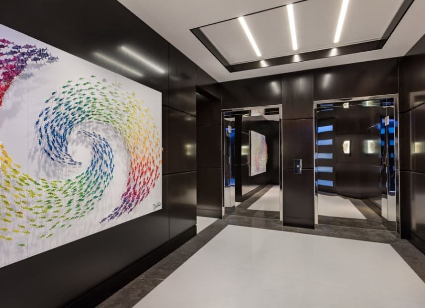 A modern black foyer with artistic and colorful wall decor. There are two elevators as well.