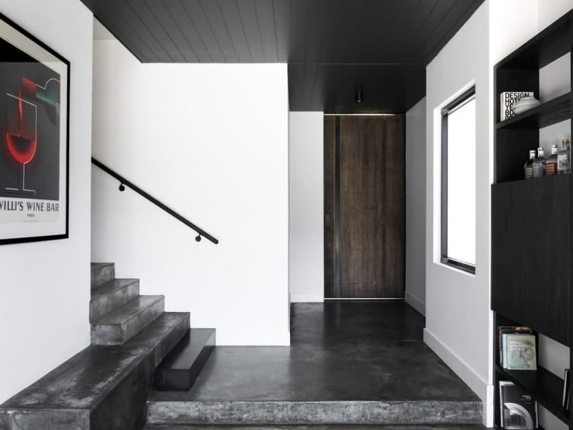 This foyer features white walls and black floors along with a black ceiling.