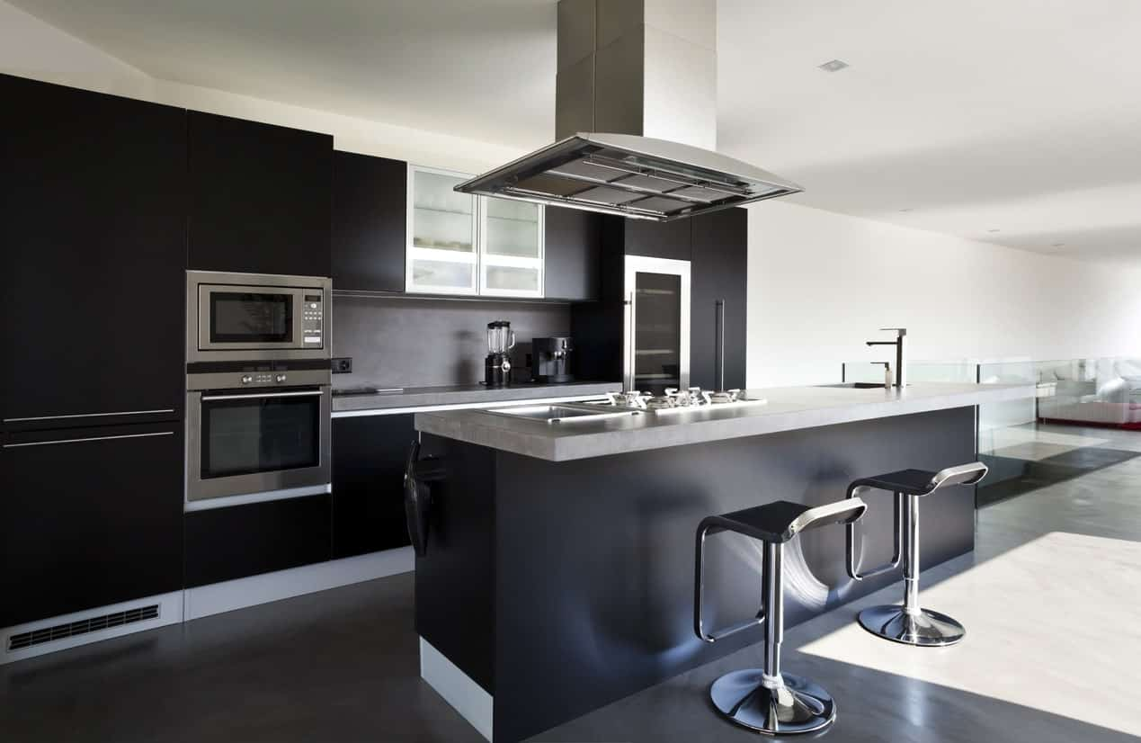 Modish kitchen featuring black kitchen counter and island with a modish bar stools.