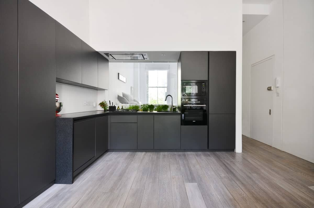 Spacious L-shape kitchen featuring black kitchen counters and countertops. The room features hardwood flooring.