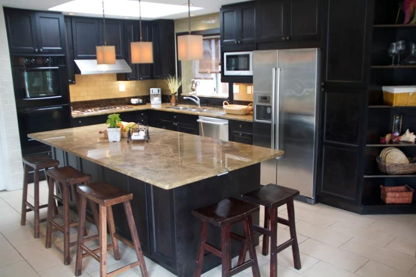 A kitchen featuring black counters and cabinetry. The kitchen counters and island feature brown countertops.