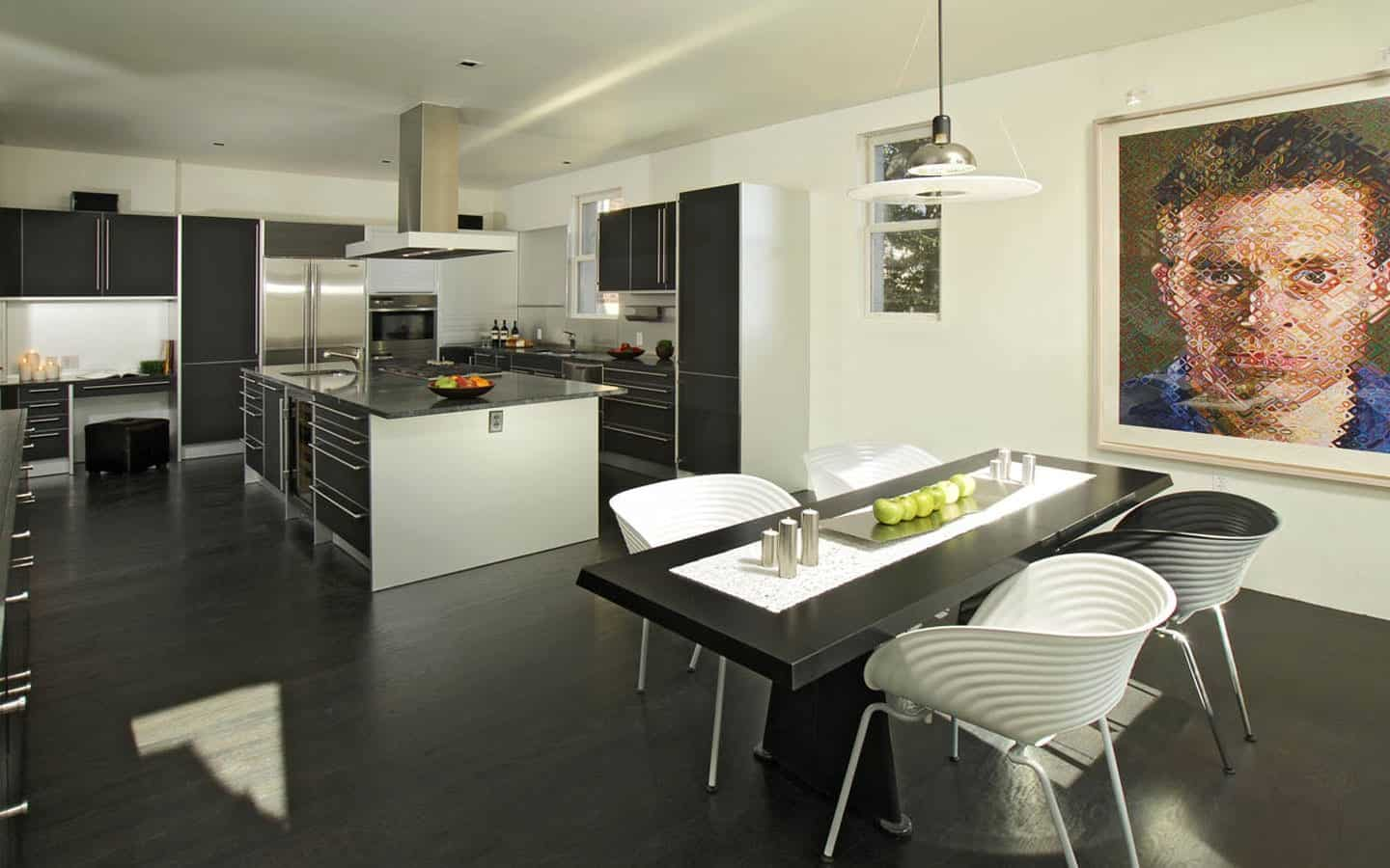Spacious dine-in kitchen featuring black hardwood flooring and a black dining table for four.
